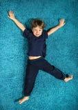 Junge, der auf dem Teppich liegt Stockfotografie