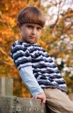 Junge, der auf dem Zaun sitzt Stockfotos