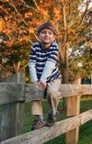 Junge, der auf dem Zaun stradling ist Lizenzfreies Stockfoto