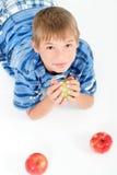 Junge, der auf den Fußboden anhält einen Apfel legt Lizenzfreies Stockfoto
