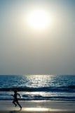 Junge, der auf den Strand läuft lizenzfreie stockfotos