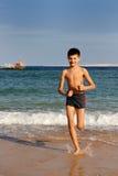 Junge, der auf den Strand läuft lizenzfreie stockfotografie