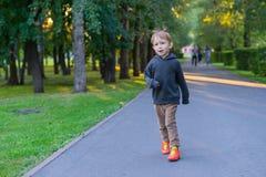 Junge, der auf der Straße im Park läuft Lizenzfreie Stockfotos