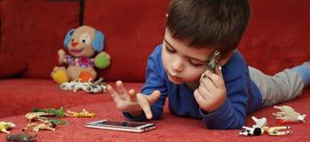 Junge, der auf der Tablette, Innen spielt Stockbild
