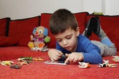 Junge, der auf der Tablette, Innen spielt Stockfotografie