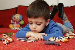 Junge, der auf der Tablette, Innen spielt Lizenzfreie Stockfotografie