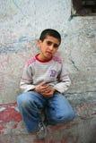 Junge, der auf der Wand sitzt Stockfotos