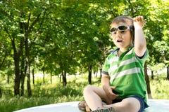 Junge, der auf die Oberseite eines Autos mit einem Telefon sitzt Stockbild