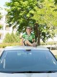 Junge, der auf die Oberseite eines Autos oben schaut sitzt Lizenzfreie Stockfotos