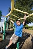Junge, der auf Dschungelgymnastik - Vertikale schwingt stockbild