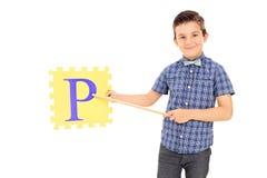 Junge, der auf ein Stück des Puzzlespiels mit einem Stock zeigt Stockbilder