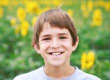 Junge, der auf einem Blumen-Gebiet lächelt Stockfoto