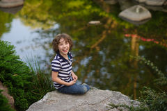 Junge, der auf einem Flussstein im kleinen Teich sitzt Stockbilder