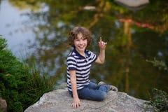 Junge, der auf einem Flussstein nahe dem Wasser sitzt Lizenzfreie Stockfotos