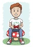 Junge, der auf einem Pilz spielt Videospiel sitzt Stockfotografie