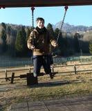 Junge, der auf einem Schwingen in einem Spielplatz in den Bergen spielt Lizenzfreies Stockbild
