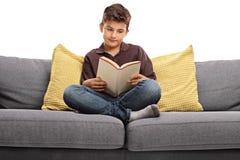 Junge, der auf einem Sofa sitzt und ein Buch liest Lizenzfreie Stockbilder