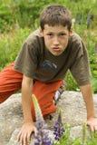 Junge, der auf einem Stein an einer Wiese aufwirft Lizenzfreies Stockfoto