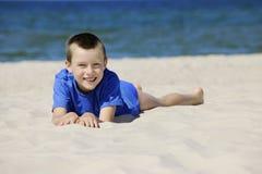 Junge, der auf einem Strand liegt lizenzfreies stockbild