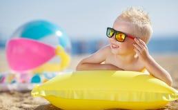Junge, der auf einer aufblasbaren Matratze ein Sonnenbad nimmt Stockbilder