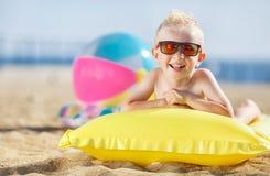 Junge, der auf einer aufblasbaren Matratze ein Sonnenbad nimmt Stockbild