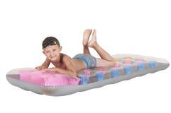 Junge, der auf einer aufblasbaren Matratze liegt Stockfoto