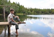Junge, der auf einer Brücke sitzt Lizenzfreie Stockfotos