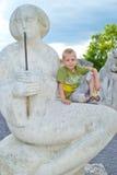 Junge, der auf einer Steinstatue sitzt Stockfoto