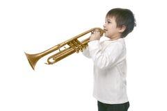 Junge, der auf einer Trompete spielt lizenzfreie stockfotos