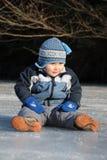 Junge, der auf Eis sitzt Stockfotos