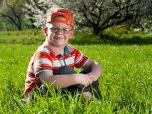 Junge, der auf Feld des Grases sitzt Stockfoto