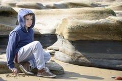 Junge, der auf Felsen sitzt stockbild