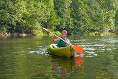 Junge, der auf Fluss canoeing ist Stockbilder