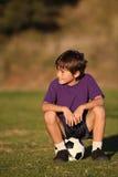Junge, der auf Fußballkugel sitzt Stockbilder