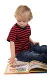 Junge, der auf Fußboden mit Buch sitzt Stockbilder