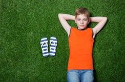 Junge, der auf grünem Gras mit Pantoffeln liegt Stockbild