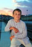 Junge, der auf großem Beutel auf Plattform des Gleiss sitzt Stockfotos