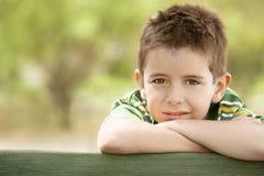 Junge, der auf hölzernem Geländer sich lehnt Stockbilder