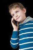 Junge, der auf Handy und dem Lächeln spricht Stockfotografie