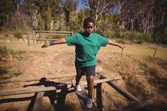 Junge, der auf Hindernis während des Hindernislaufs geht lizenzfreies stockfoto