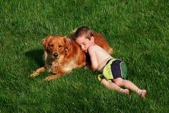 Junge, der auf Hund schläft Stockfotografie