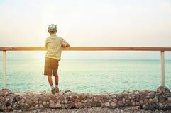 Junge, der auf Kai in der Dämmerung betrachtet Meer steht Stockfotos