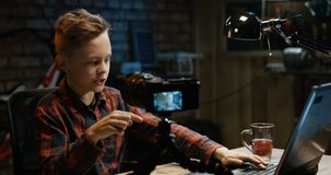 Junge, der auf Kamera in einer Garage spricht stock video