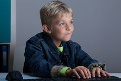 Junge, der auf Laptop spielt Stockfotografie