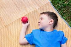 Junge, der auf Matte und Blick am Apfel legt Lizenzfreies Stockfoto