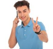 Junge, der auf Mobile spricht und das Siegeszeichen zeigt Stockfotografie