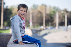 Junge, der auf Rand der Granitbeschränkung, copyspace sitzt Stockfotos