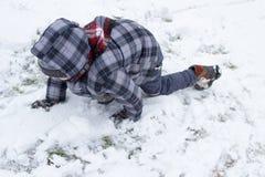 Junge, der auf Schnee klettert Stockfotos