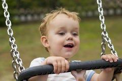 Junge, der auf Schwingen lächelt Stockbilder