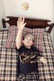 Junge, der auf seine BettwarteBaseballsaison legt Lizenzfreie Stockfotografie